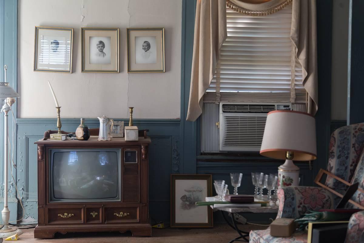 Photos hang on the wall above a vintage television.