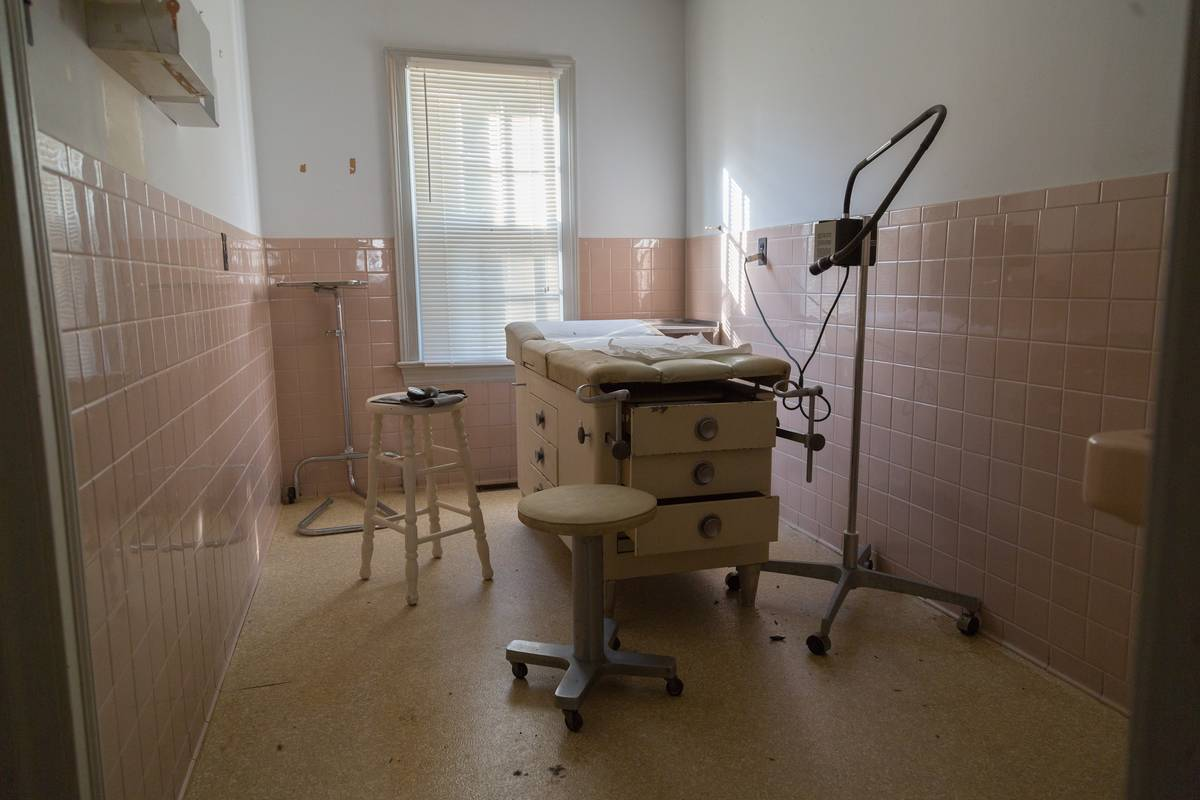 An examination room has a patient bed.