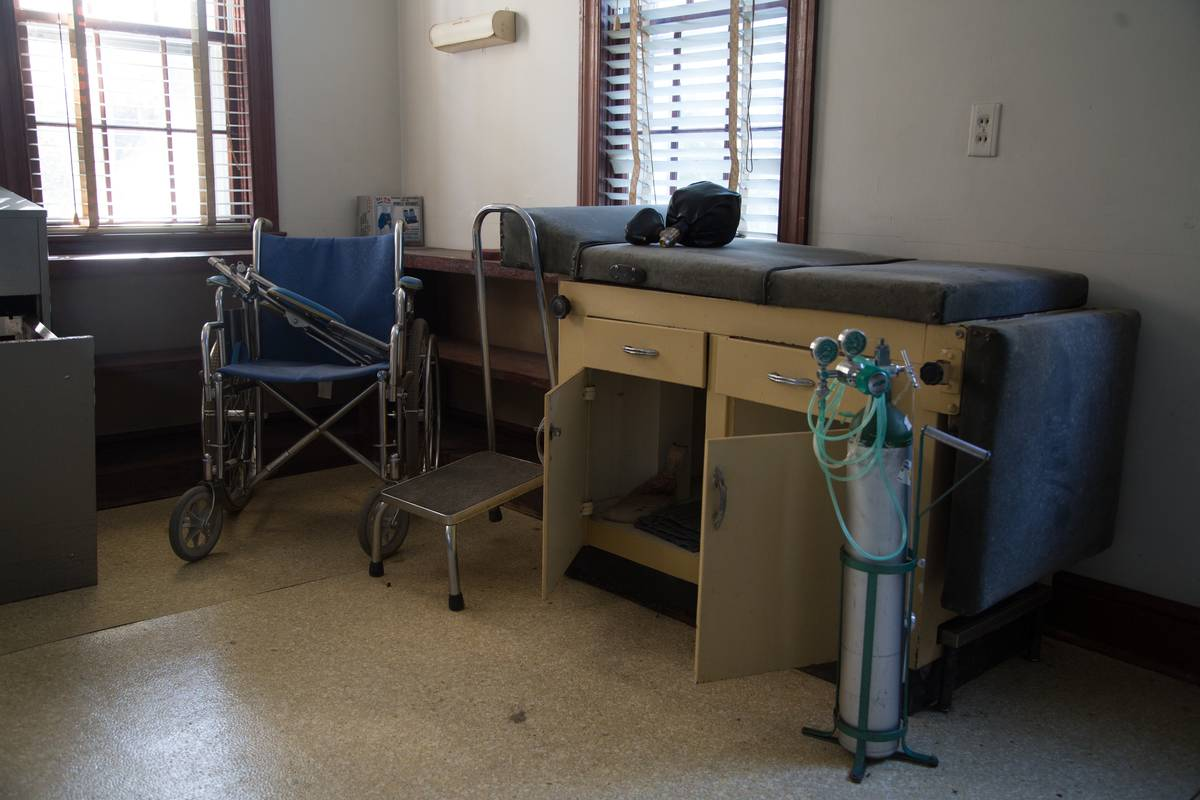 A room has a wheelchair and an oxygen tank.