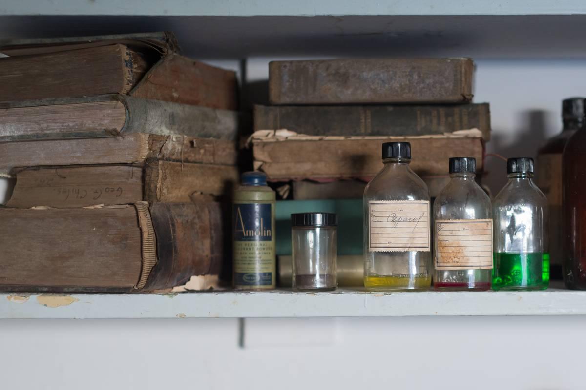 A closeup shows rundown books and medicine bottles.