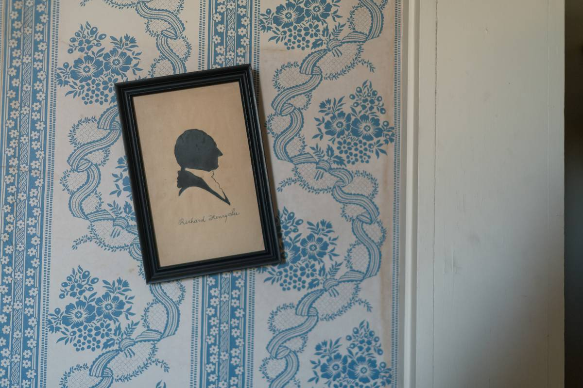 A crooked frame holds a profile silhouette of a man.