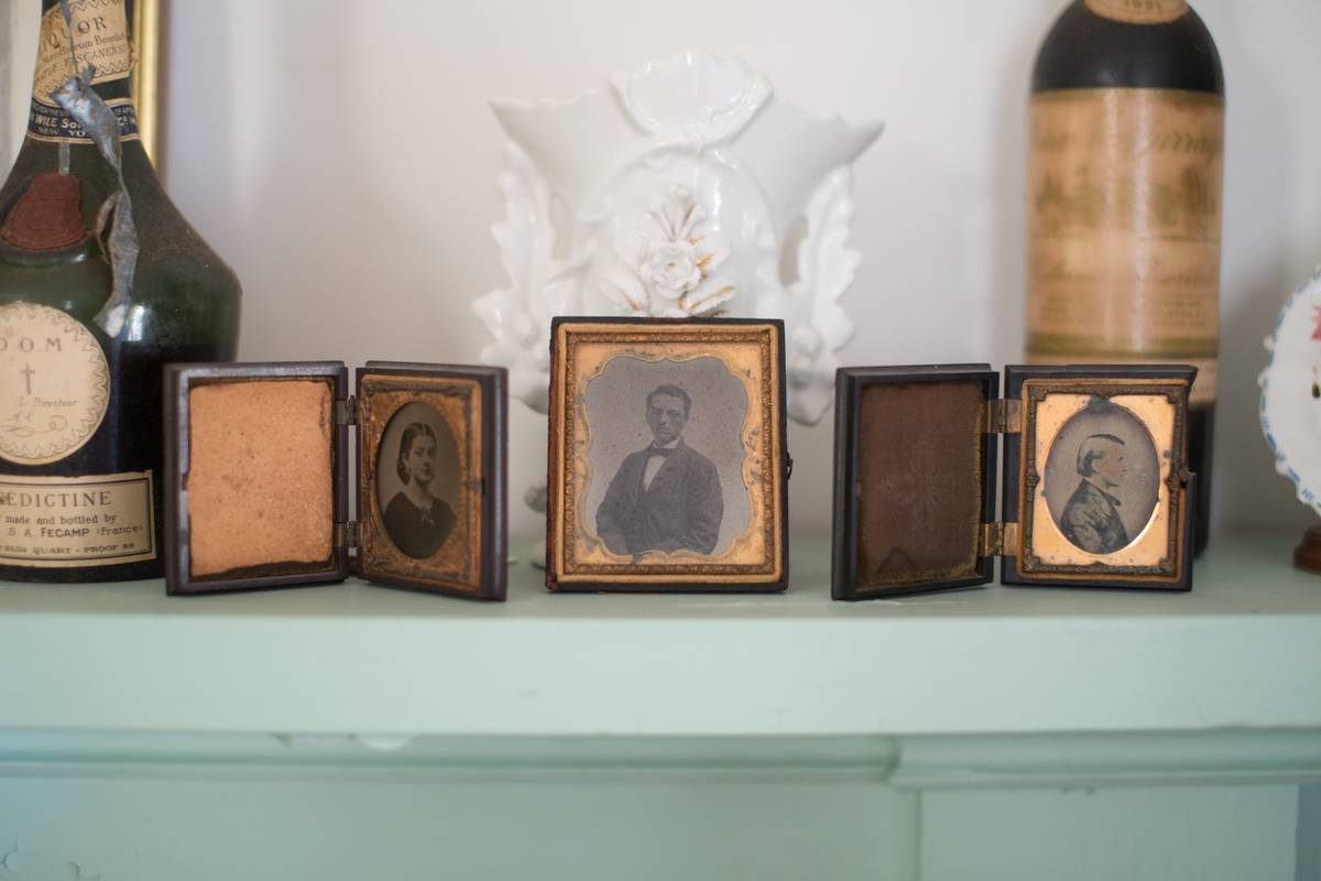 A close-up of the fireplace shows vintage photographs.