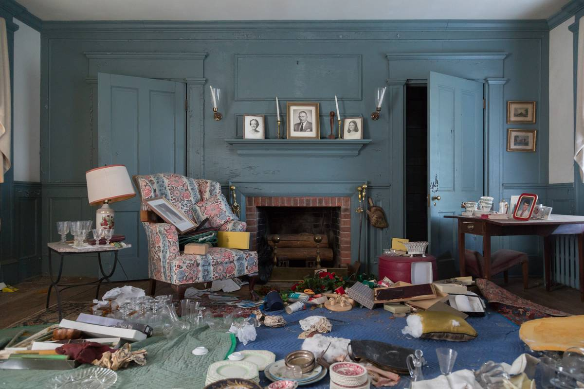 A parlor is covered with abandoned items.