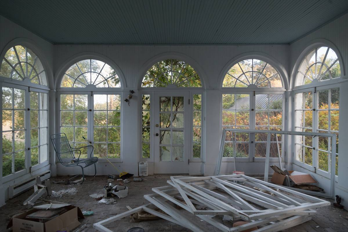 A pile of window frames sits in a sunroom.
