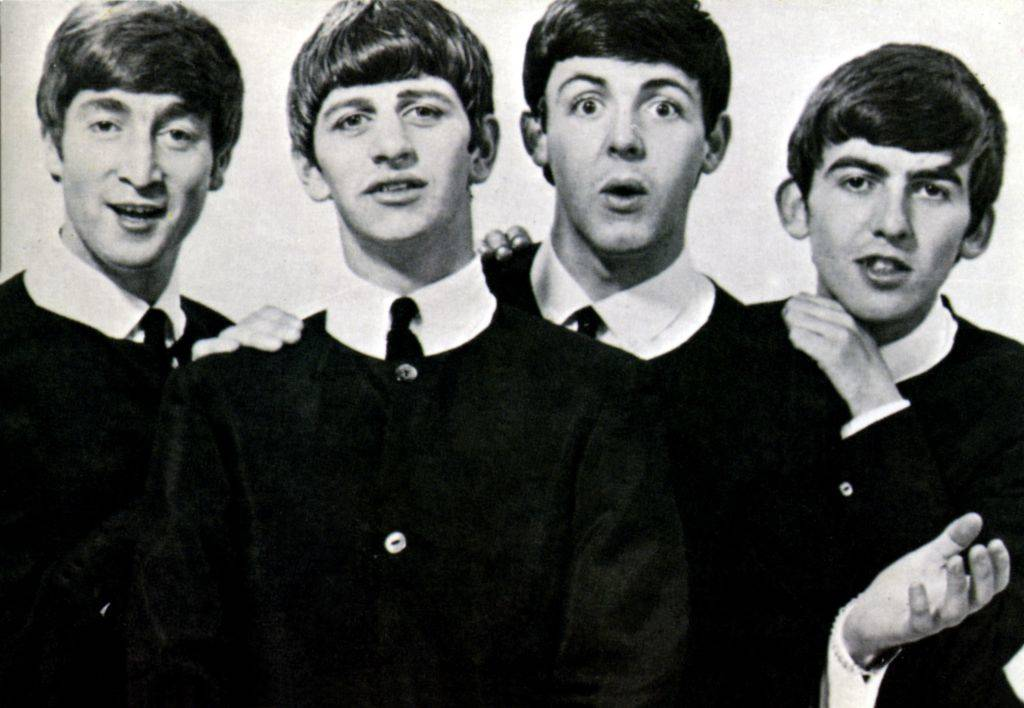The Beatles pose in their schoolboy look.