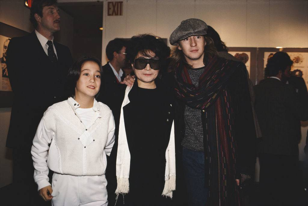 Teenage Julian and young Sean Lennon put their arms around Yoko Ono.