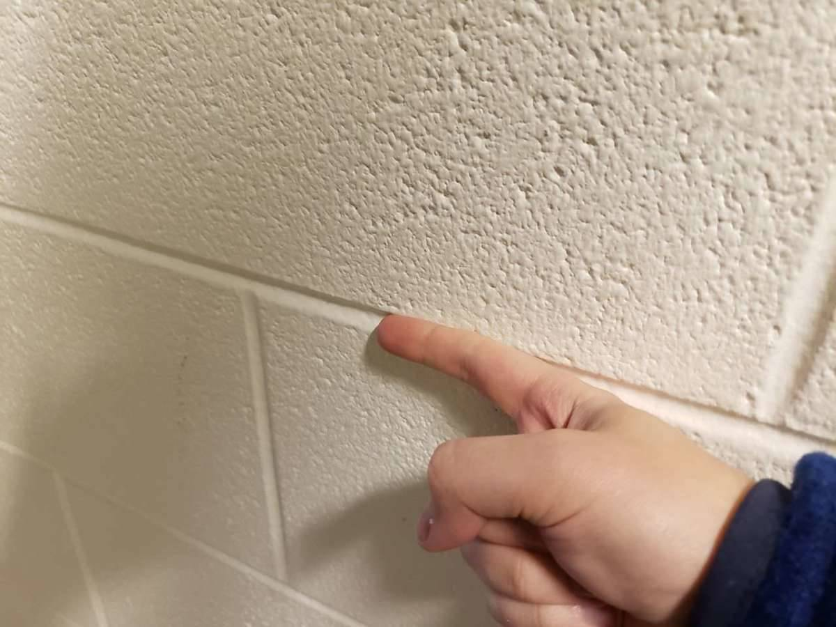 running finger along the grooves in the wall