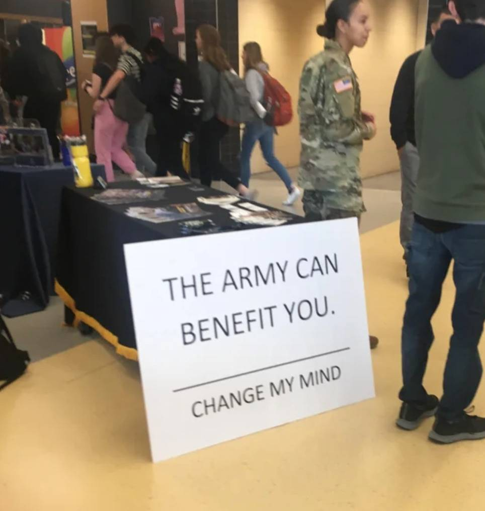 recruitment booth uses meme: THE ARMY CAN BENEFIT YOU. CHANGE MY MIND