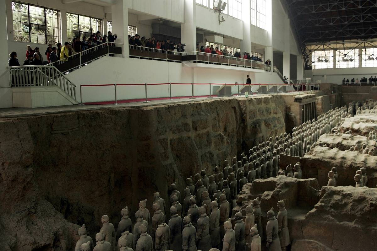 Tourists look down at the pit of terracotta soldiers.