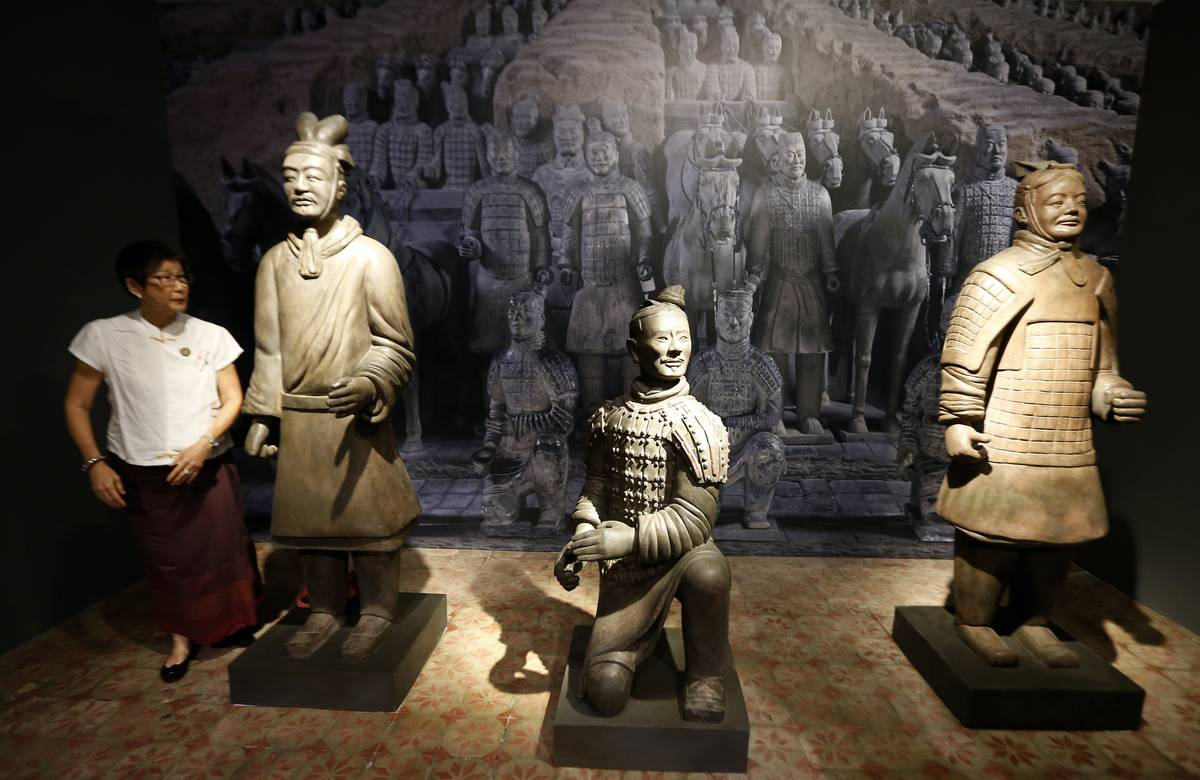 A visitor poses near terracotta soldiers at the National Museum of Thailand.
