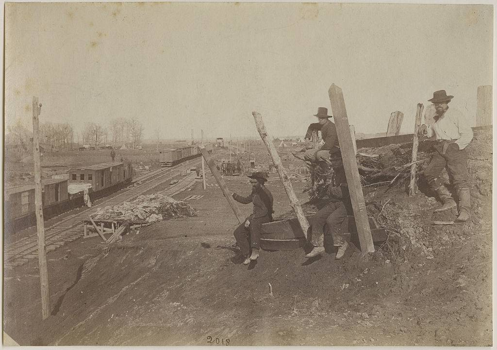 Men sitting by a railroad