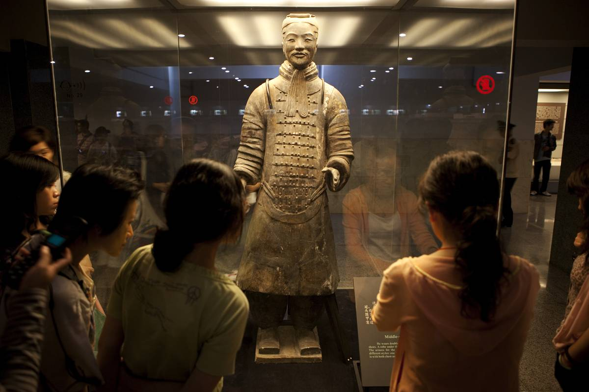 Tourists converge on a glass case holding a Terracotta Warrior at the Terracotta Warriors Museum.