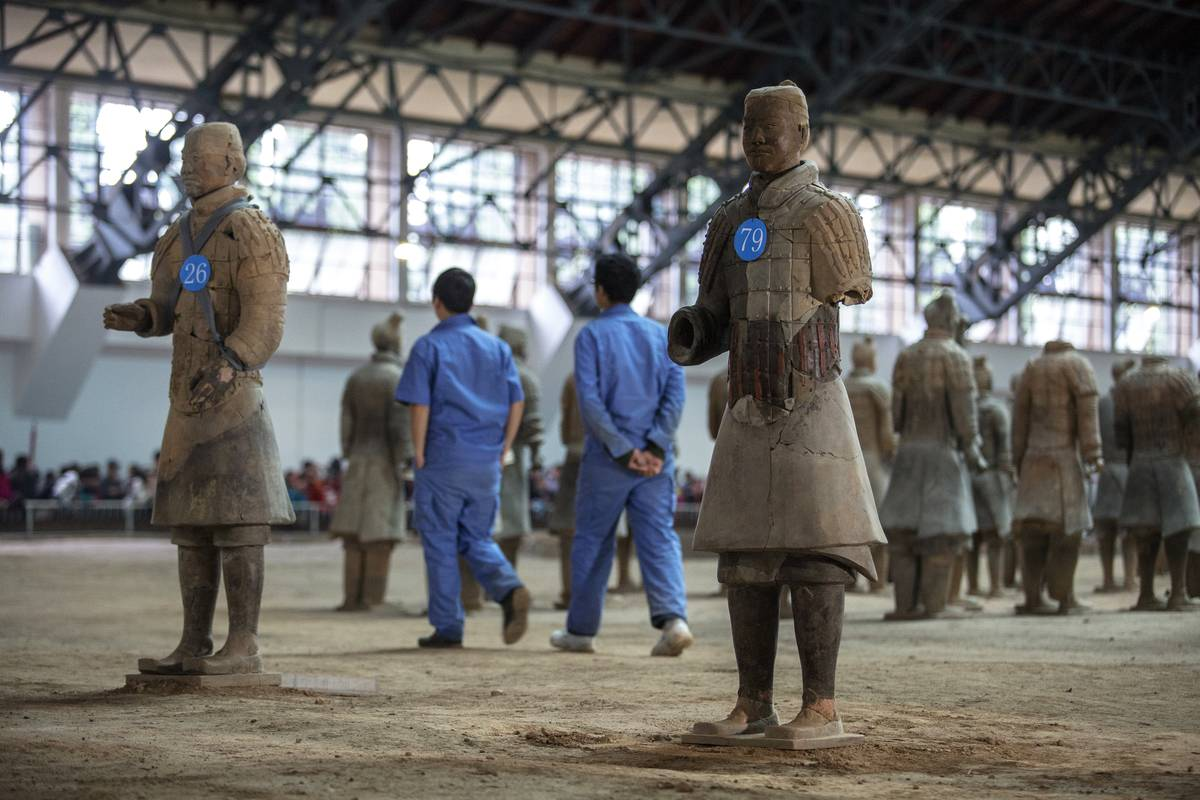 Archaeologists set out labeled statues for repair.