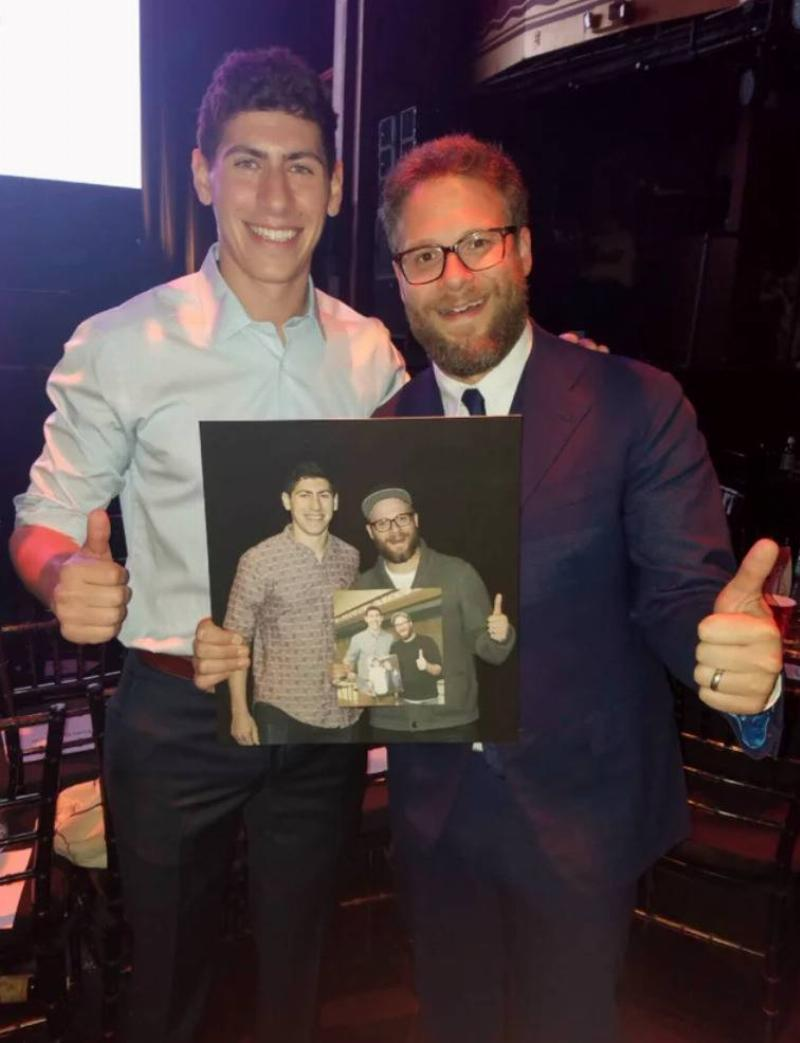 man with seth rogan holds photo of them in the same pose holding an even older photo of them in the same pose
