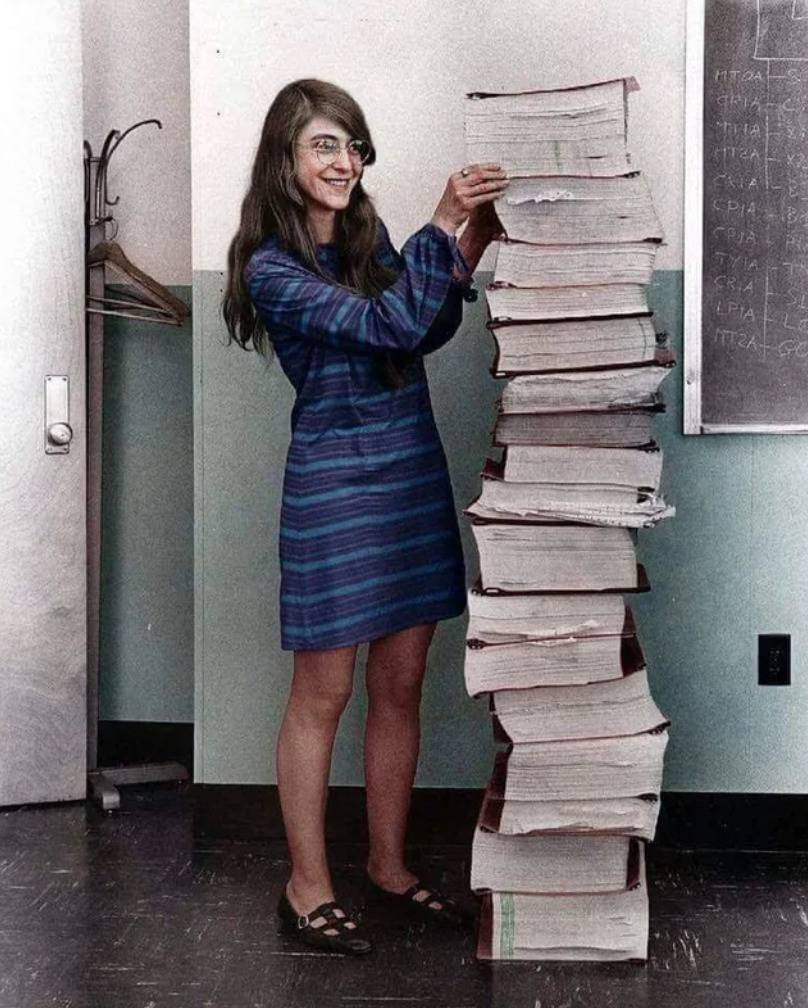 woman stands next to stack of books as tall as her
