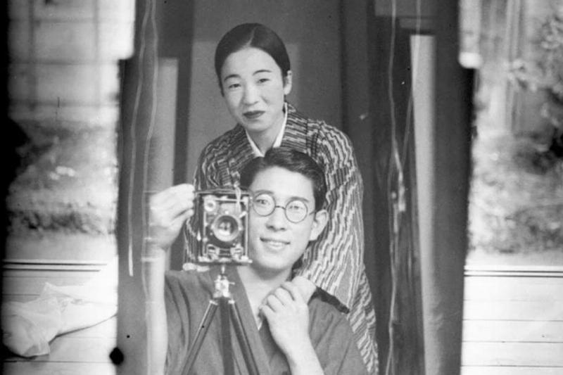 couple take black and white selfie in mirror with old camera
