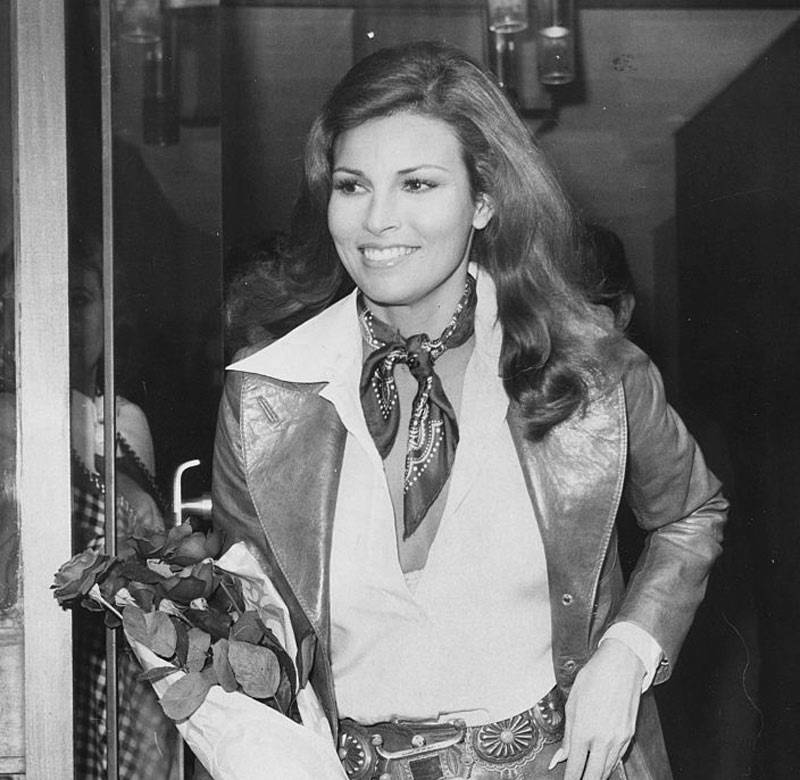 Actress Raquel Welch carrying a bouquet of roses as she leaves the studio after filming an interview for 'On the Ball', London, November 9th 1972.