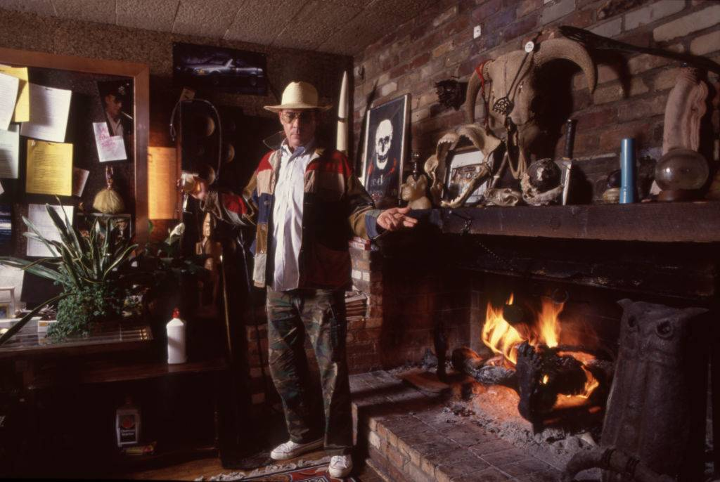 Hunter Thompson aka Hunter S Thompson aka Gonzo Journalist at his ranch standing next to his fireplace