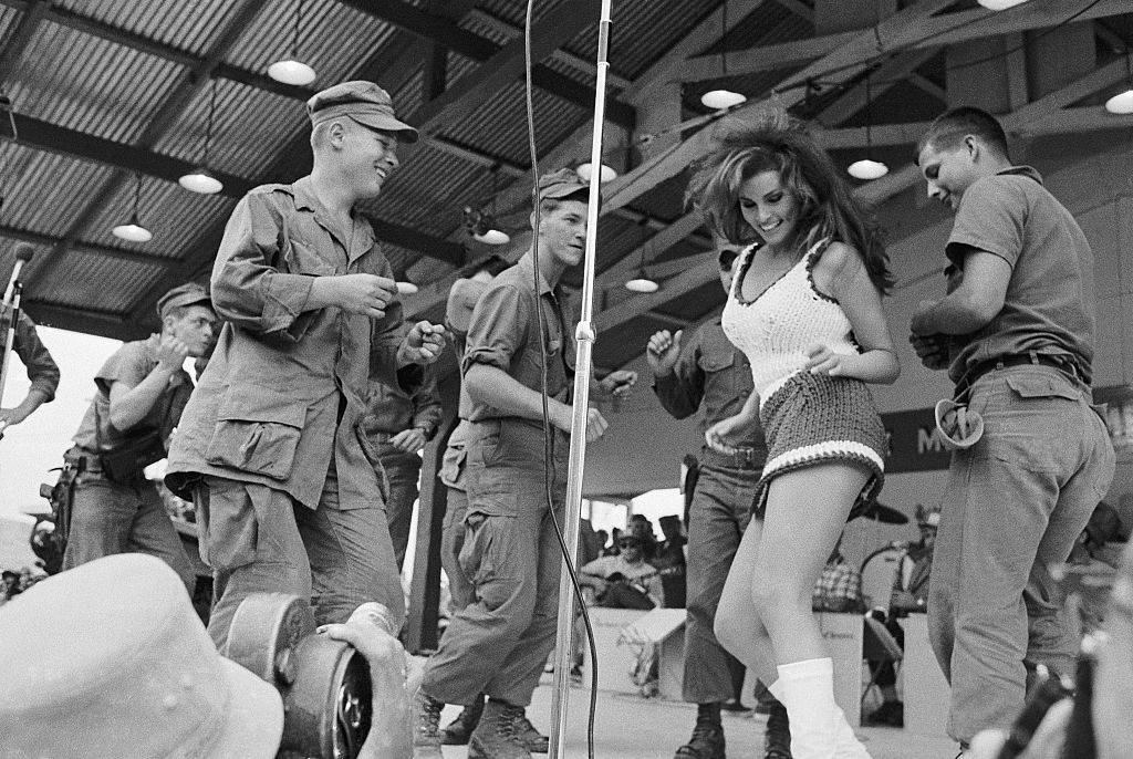Raquel Welch dances on stage with a group of soldiers during a Bob Hope USO show at Da Nang, Vietnam.
