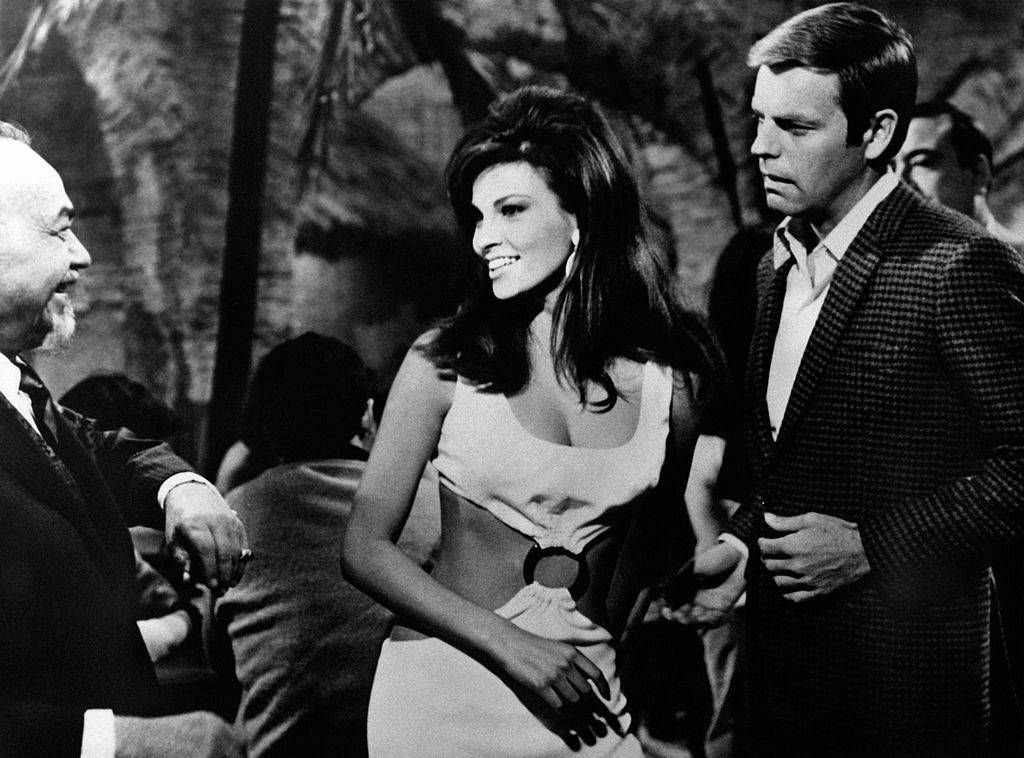 WAmerican actress Raquel Welch (Jo Raquel Tejada) smiling to American actor Robert Wagner in the film The Biggest Bundle of Them All. American actor Godfrey Cambridge is watching them. 1968