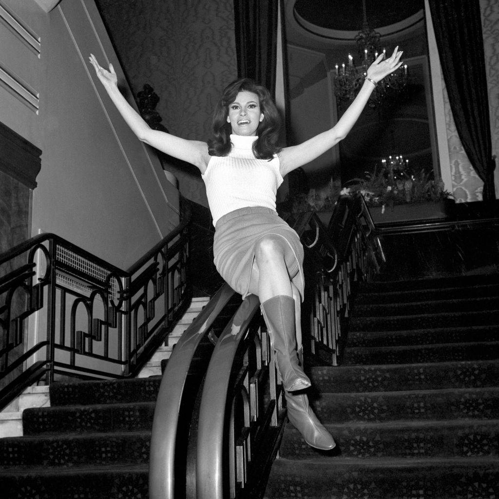 Raquel Welch star of One Million Years BC makes an entrance by sliding down the stair rail at the Odeon Leicester Square during a rehearsal for the appearance at the Royal Film Performance.