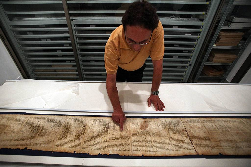 Man examining the Dead Sea Scroll