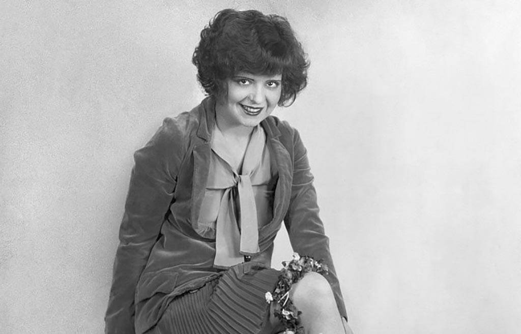 Clara Bow sitting on a bench