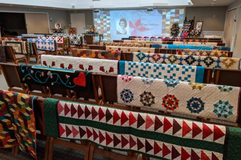 quilts cover all the pews at a funeral ceremony