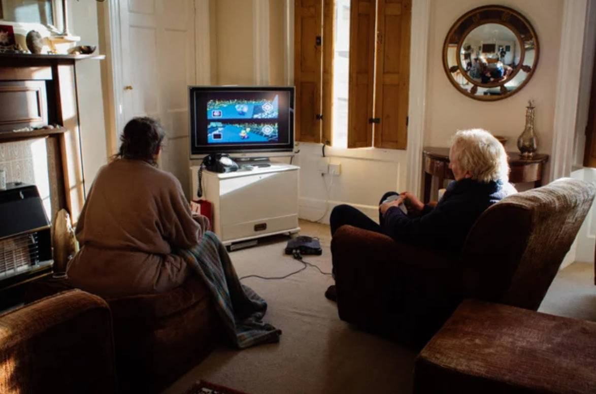 two elderly people playing mario kart in their living room