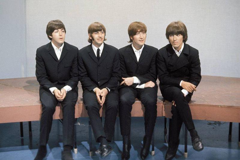 beatles sitting on a bench wearing matching suits