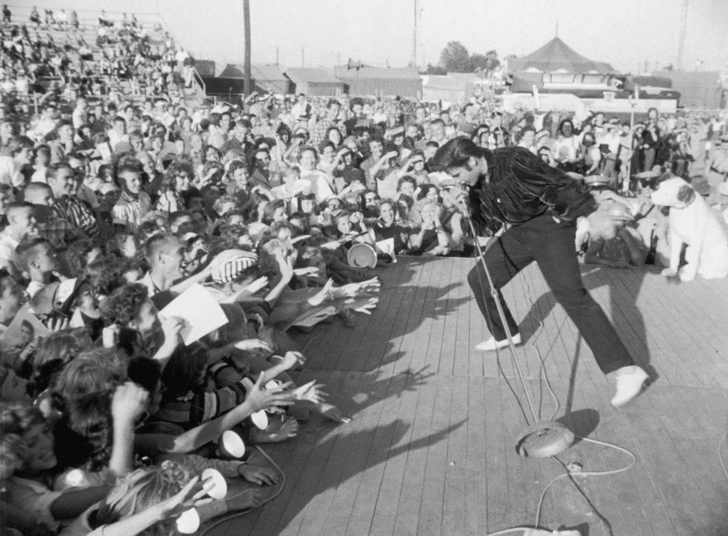 elvis presley performing to a crowd of teens