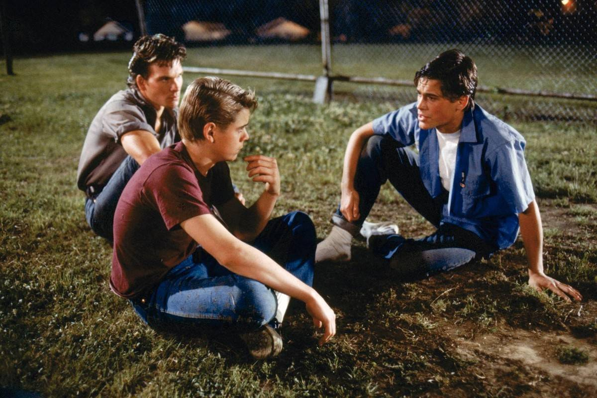 Lowe, Swayze and Howell sitting in the grass