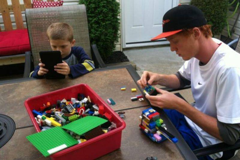 a child on an iPad, an adult playing with Lego