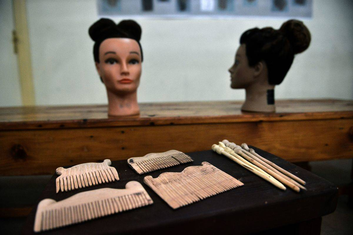 Ancient combs are displayed in from of ancient Greek hairstyles in a museum.