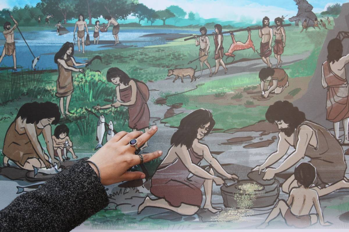 A woman points at a picture of ancient people cooking in the Indus Valley.