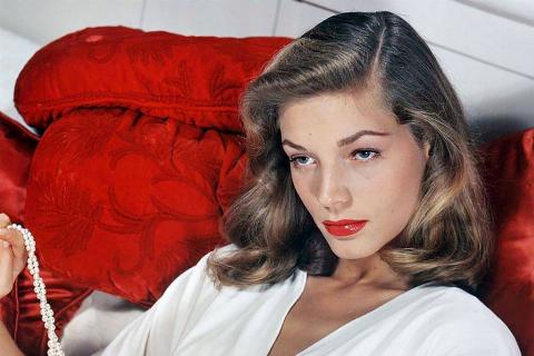 Lauren Bacall on a red couch