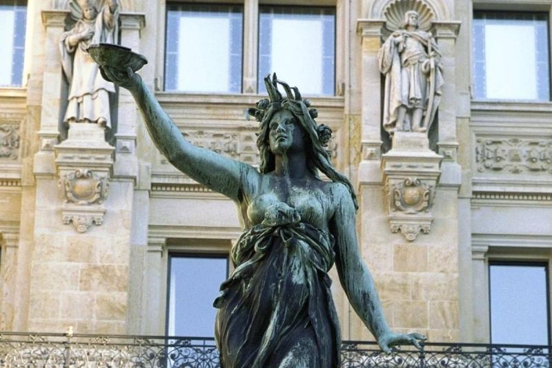A statue of the Greek goddess Hygieia stands on top of a fountain.