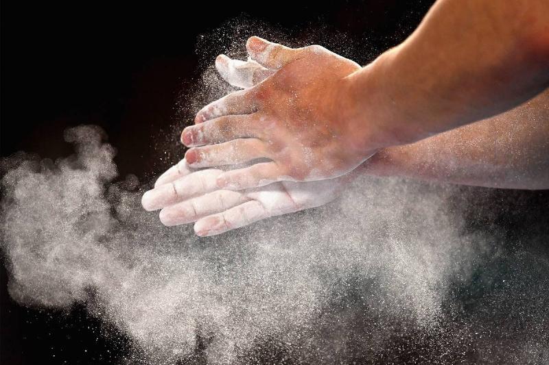 A gymnast rubs chalk powder on his hands.