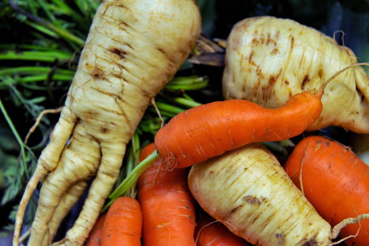 A pile of vegetables appear in a farmer's market.