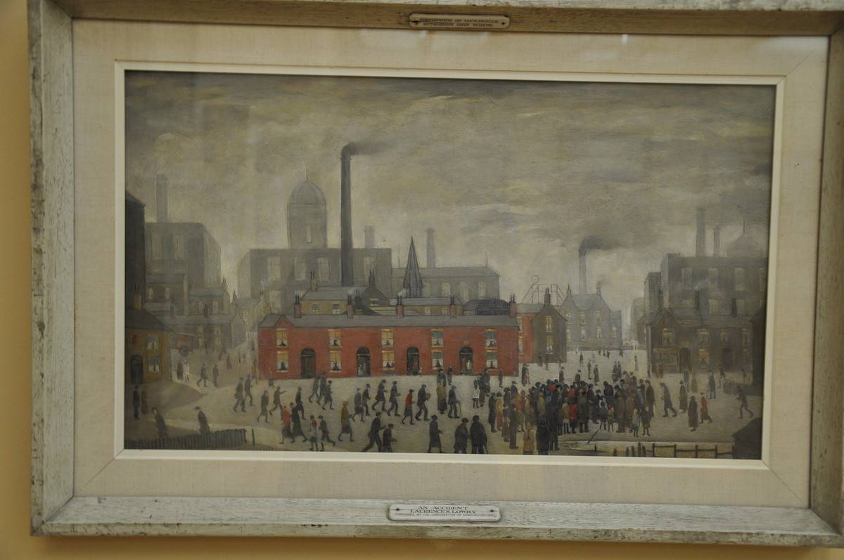 A white frame holds the artwork An Accident by LS Lowry.