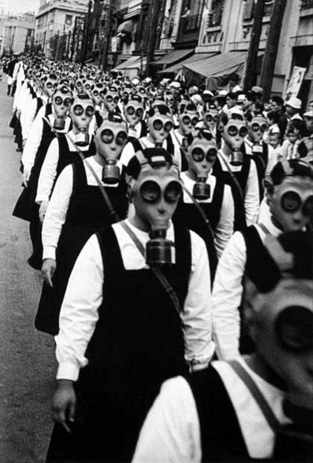 Japanese school girls march through the streets wearing gas masks.