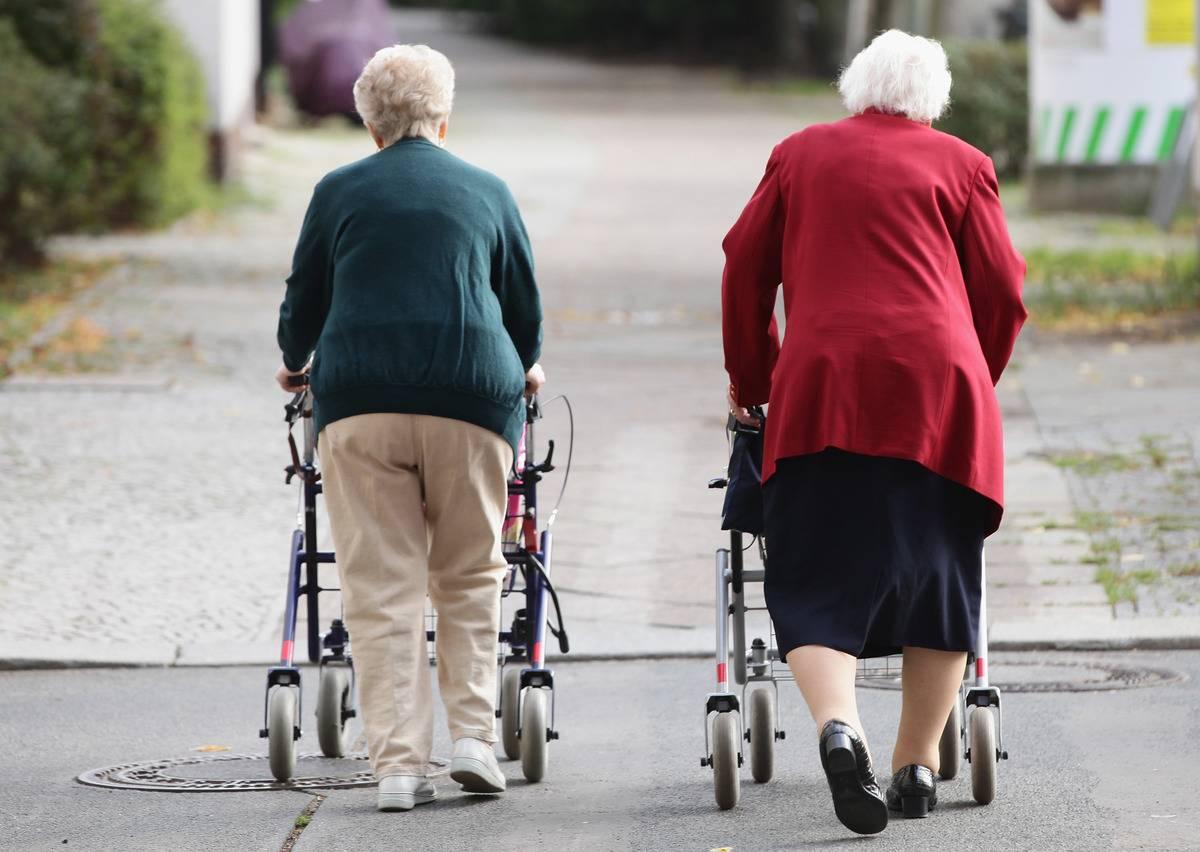 Two elderly women push shopping carts down a street