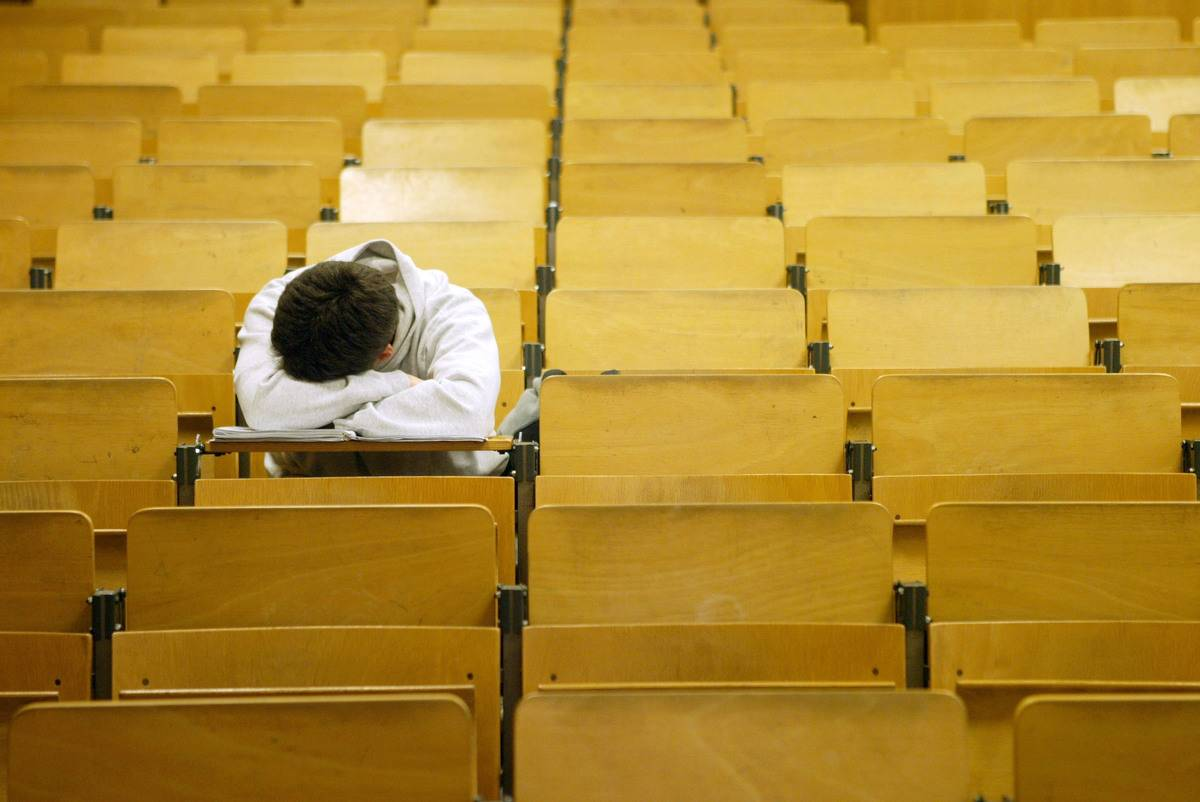 A student naps in a lecture hall