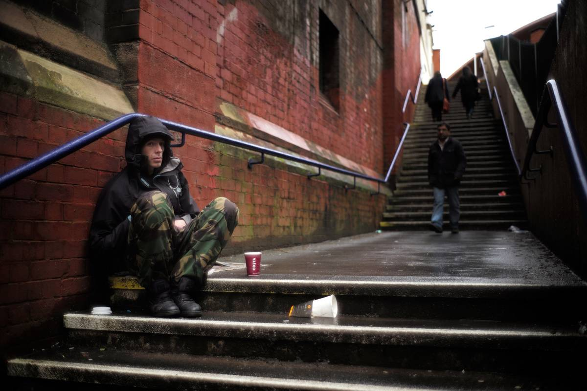 A man begs for loose change on the streets of Manchester