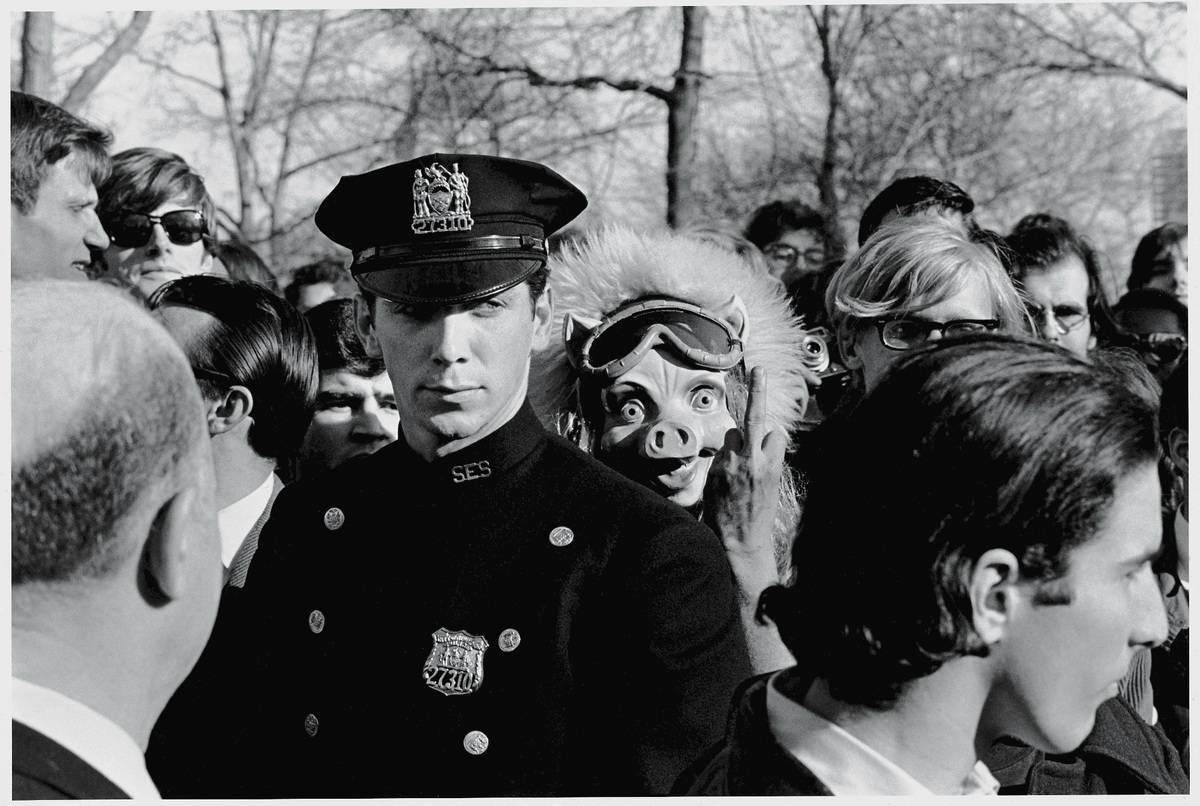 An American policeman watches over the crowd as a protestor in a pig mask stands over his shoulder and gives the camera 'the finger.'