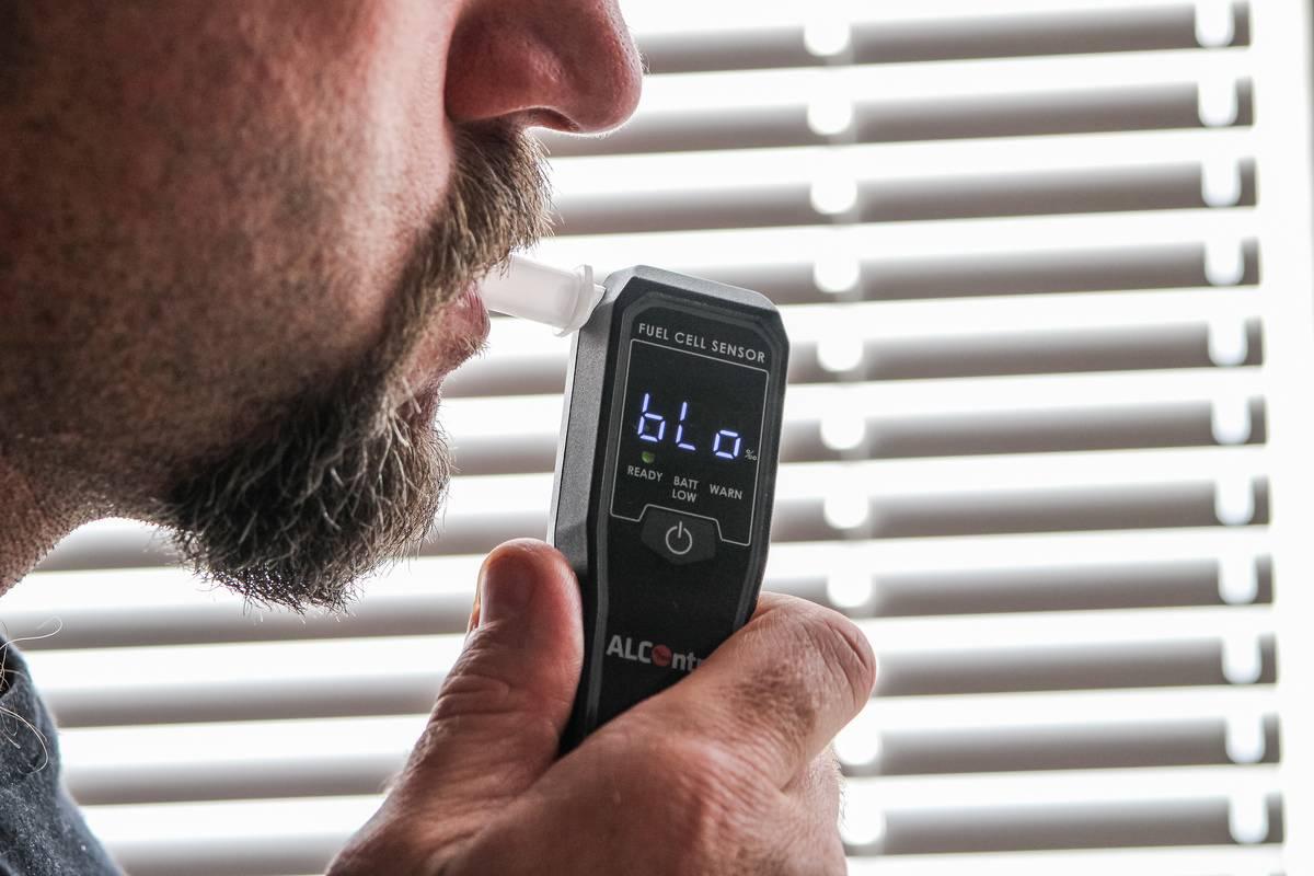 man blowing in breathalyzer