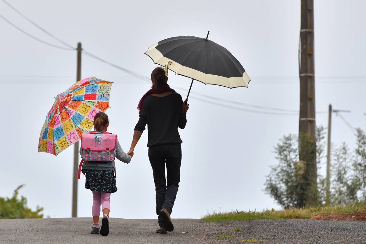 A girls walks to her primary school with her mother