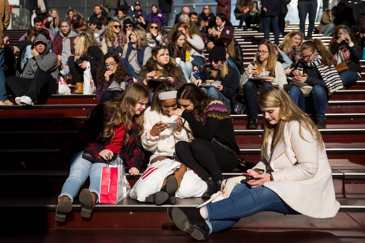A group of teens look at a photograph they took on a smartphone in Times Square