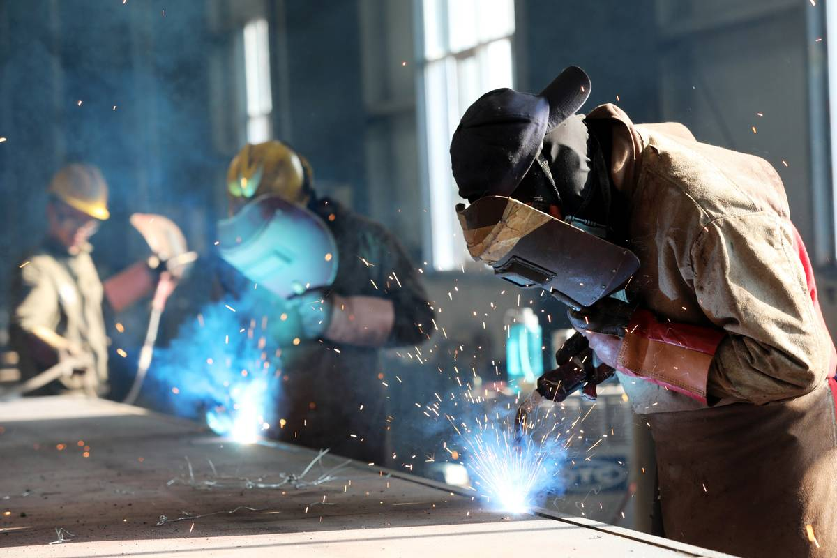 worker cutting steel at a factory