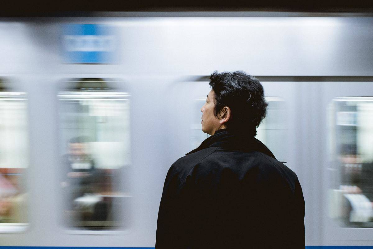 man in front of moving subway train